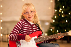 Girl with guitar in front of Christmas tree Royalty Free Stock Images