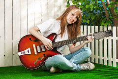Girl with a guitar in the garden Royalty Free Stock Images