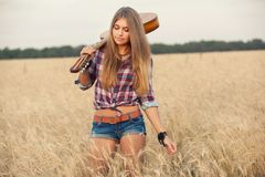 Girl with guitar goes on wheat field Royalty Free Stock Photo