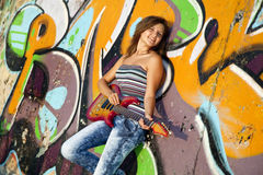 Girl with guitar and graffiti wall Royalty Free Stock Photo