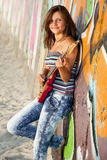 Girl with guitar and graffiti wall Stock Photography