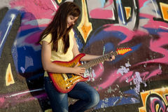 Girl with guitar and graffiti wall Royalty Free Stock Image