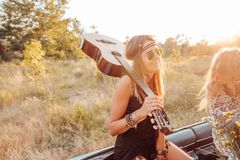 A girl with a guitar in the car. A girl with a guitar on her shoulder is sitting in the car Stock Images