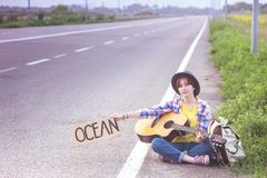 Girl with a guitar hitch-hiking. Young girl with a guitar coming along the road and hitch-hiking royalty free stock photo