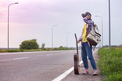 Girl with a guitar hitch-hiking. Young girl with a guitar coming along the road and hitch-hiking stock photography