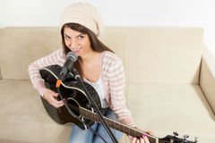 Girl with a guitar and microphone Stock Images