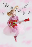 Girl with guitar on music notes background Royalty Free Stock Photos