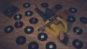 Girl with a guitar among the records.