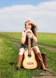 Girl with a guitar on the road Royalty Free Stock Images