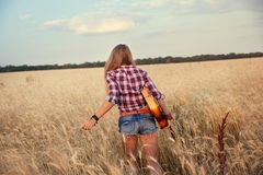 Girl with a guitar running through the wheat field Royalty Free Stock Photos
