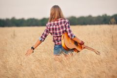Girl with a guitar running through the wheat field Royalty Free Stock Image