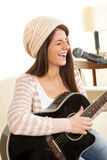 Girl with a guitar singing on microphone Royalty Free Stock Photos