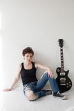 The girl with the guitar sits on the floor Royalty Free Stock Photo
