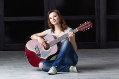 Girl with guitar sitting on the floor Royalty Free Stock Image