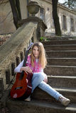 Girl With Guitar Sitting on the Stairs Outdoors on Sunny Day Royalty Free Stock Photo