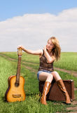 Girl with a guitar and suitcase outdoor. Pretty blond girl with a guitar and old leathern suitcase on the road Stock Image