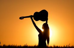 Girl with guitar at sunset. Silhouette of young attractive girl raising guitar in the air in wheat field at sunset Stock Photography