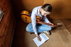 Girl with a guitar who writes a song. Girl Playing Guitar Writing Song Concept Royalty Free Stock Image