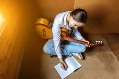 Girl with a guitar who writes a song. A woman holding guitar and learning to play song Stock Image