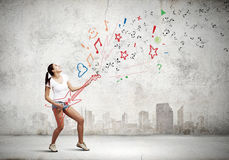 Girl with guitar. Young girl in shorts playing on imaginary guitar Royalty Free Stock Photo