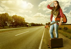 Girl with guitare and suitcase on highway Royalty Free Stock Photos