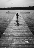 The Girl and the Gull. A Little Girl Mimics a Seagull on a Dock Royalty Free Stock Photo