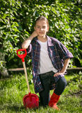 Girl in gumboots posing with toy spade at garden Royalty Free Stock Image