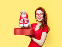 Girl with gumshoes and gift box. Smiling redhead girl with gumshoes and gift box on yellow background Royalty Free Stock Photos