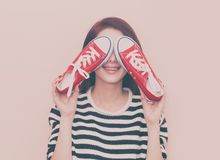 Girl with gumshoes. A young beautiful caucasian girl with gumshoes on pink background Royalty Free Stock Photos