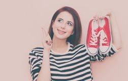 Girl with gumshoes. A young beautiful caucasian girl with gumshoes on pink background Royalty Free Stock Photo