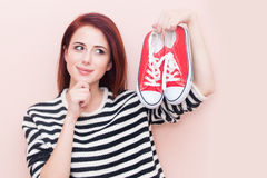 Girl with gumshoes. A young beautiful caucasian girl with gumshoes on pink background Royalty Free Stock Photography
