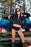 Girl with gun. Asian girl with gun by car royalty free stock photography