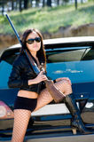 Girl with gun. Asian girl with gun by car royalty free stock images