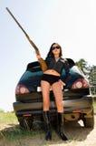Girl with gun. Asian girl with gun by car royalty free stock photo