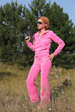 Girl with gun. The red-haired girl in a pink suit with the sports weapon in wood Royalty Free Stock Image