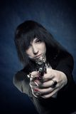 Girl with gun. Pretty gothic girl with gun posing over blue royalty free stock image