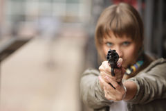 Girl and gun. Girl holding a gun in his hand royalty free stock photo