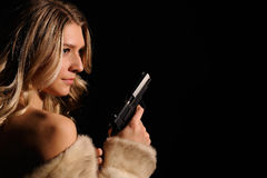 Girl with gun. Girl in a fur coat with gun Stock Image