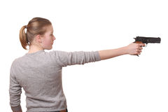 Girl with a gun. Portrait of a young teenage girl with a gun on white background stock photo