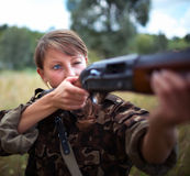 Girl with a gun aiming at a target Royalty Free Stock Image