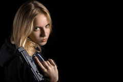 Girl with gun. Beautiful girl with gun on black background with copyspace Royalty Free Stock Images