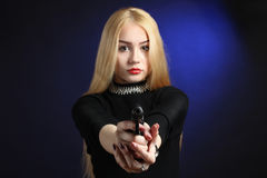 Girl with a gun. Beautiful and serious girl with pistol on dark blue background Royalty Free Stock Photo
