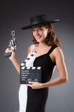 Girl with gun and clapperboard isolated on white Royalty Free Stock Photography