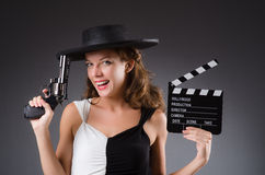 Girl with gun and clapperboard  on white Royalty Free Stock Photo