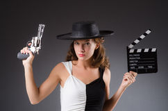 Girl with gun and clapperboard  on white Stock Photography