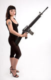 Girl with gun and headphones. Sexi girl in black dress with gun and headphones Stock Photos