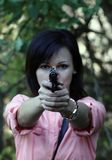 Girl with a gun in his hand. Dangerous cute girl with a pistol in hands stock photo