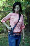 Girl with a gun in his hand. Girl pulls out a gun from the holster stock photography