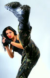 Girl with gun  in kick moving Stock Images