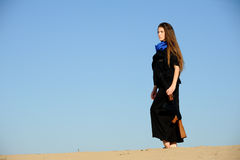 Girl with gun in the sand. The girl, dressed in black with a gun standing on top of the dunes Royalty Free Stock Photography